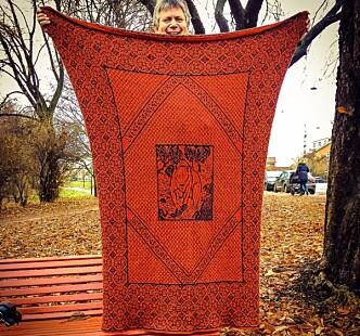 <strong>STORE TEPPER:</strong> En fordel ved å være mann som strikker er å kunne håndtere stort strikketøy, sier Kristian. Her med et egenprodusert teppe. FOTO: Privat / Facebook