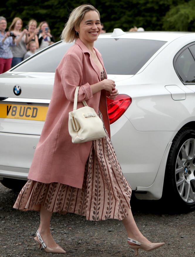 STRÅLTE: Emilia Clarke, som spiller rollen som Daenerys Targaryen i «Game of Thrones», var i strålende humør da hun ankom kirken ikledd en rosa kjole. Foto: NTB scanpix