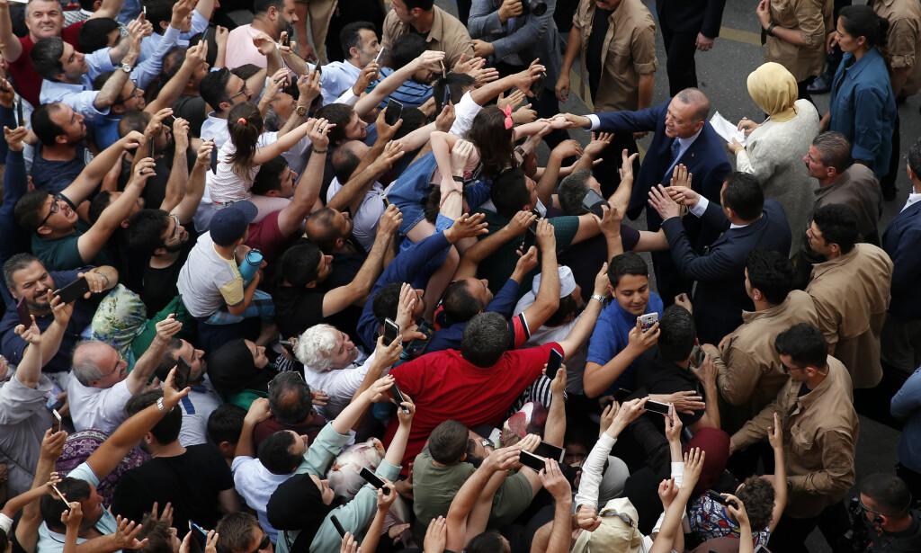 Tyrkias president Recep Tayyip Erdogan (t.h) trykket hendene til noen av sine tilhengere da han avla sin stemme i søndagens valg. Foto: AP / NTB scanpix