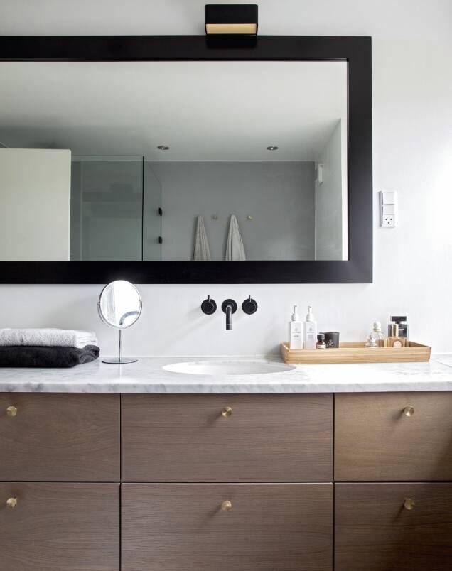 Badet er, akkurat som kjøkkenet, i tre, med messingknotter fra Københavns Møbelsnedkeri, og gir en moderne utgave av shakerstilen med benkeplate i grå marmor. FOTO: Iben og Niels Ahlberg
