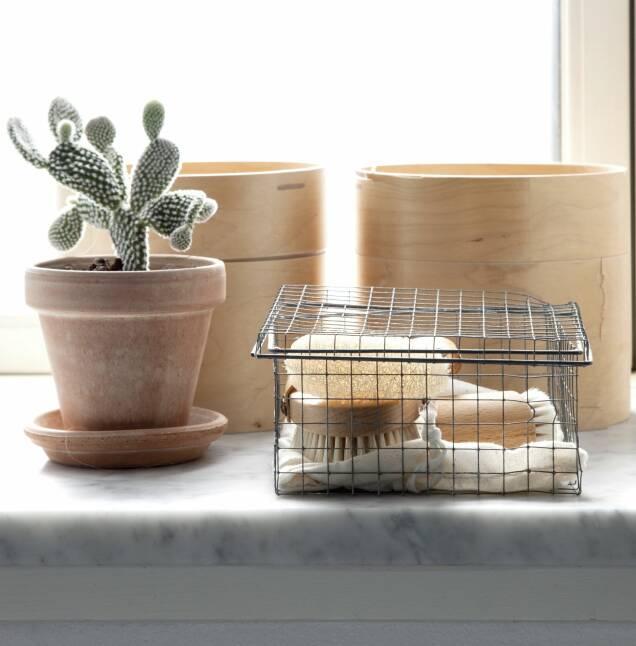 Bruk bokser og esker i tre for å understreke den rene stilen. Sammen med en trebørste og en enkelt plante skaper du liv, uten at det blir overpyntet. FOTO: Iben og Niels Ahlberg