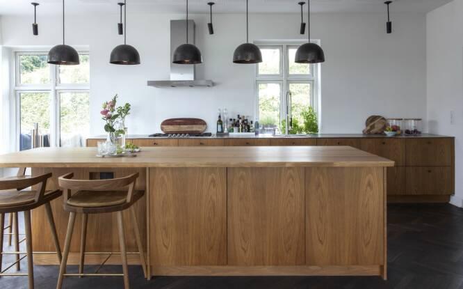 Har du plass til en stor kjøkkenøy, bør du anvende kun én del til skap og la halvdelen være et innhakk. På den måten får du spiseplasser der det er god plass til beina. Barstolene er, som kjøkkenet, fra Københavns Møbelsnedkeri. FOTO: Iben og Niels Ahlberg