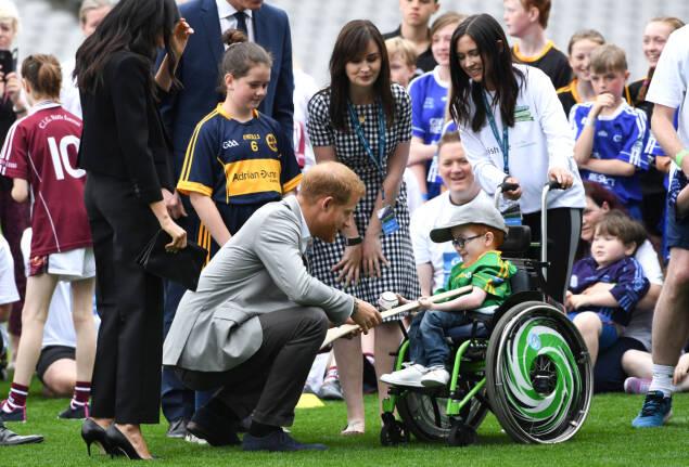STORT ØYEBLIKK: Prins Harry slår av en prat med en liten tass som stolt viser frem baseball-utstyret sitt. Foto: NTB Scanpix