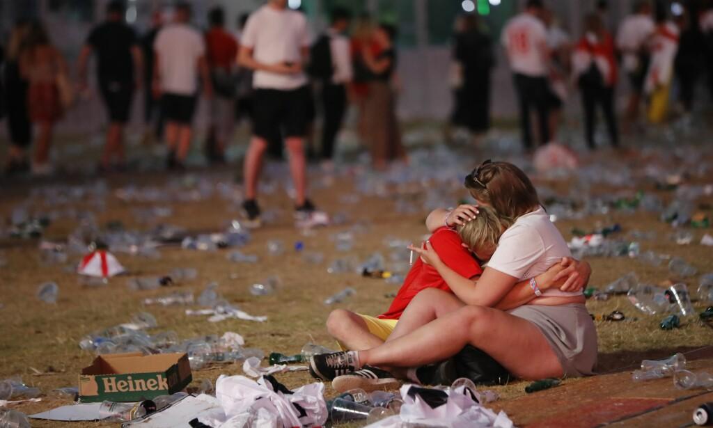 STÅR - ELLER SITTER SAMMEN: Britene etter VM-tapet. Dette bildet oppsummerer stemningen i Hyde Park. Foto: AFP PHOTO / Tolga AKMEN