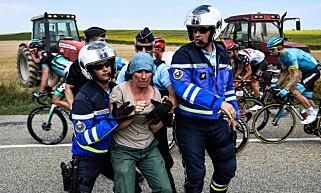 TATT: En aktivist blir tatt hånd om av politiet. Foto: NTB Scanpix