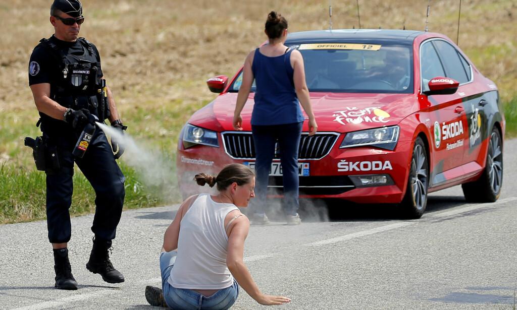 FIKK GJENNOMGÅ: En politimann bruker pepperspray på en sittende demonstrant. Foto: NTB Scanpix
