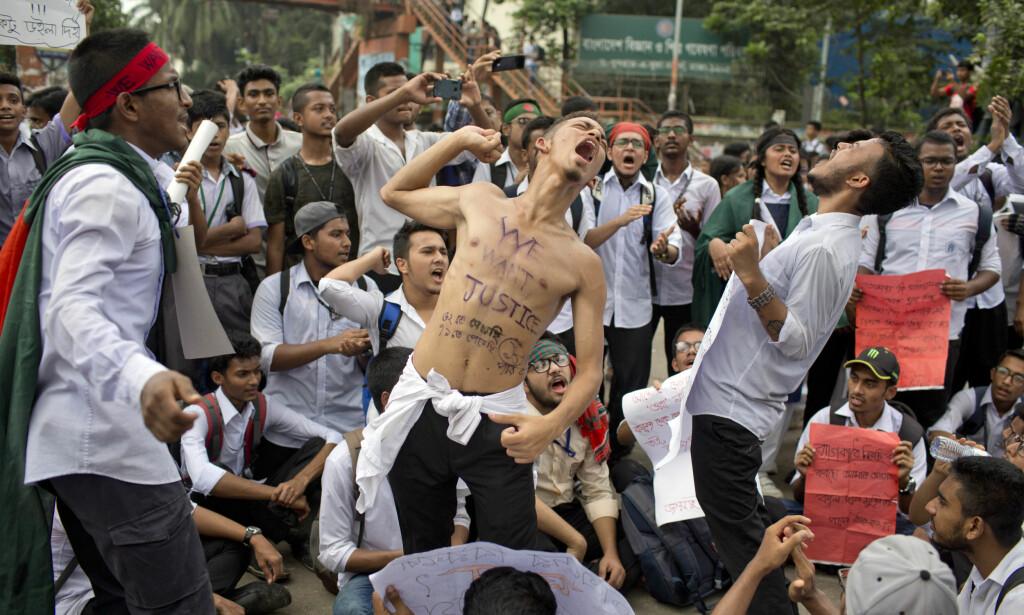 KREVER RETTFERDIGHET: - Vi vil ha rettferdighet, står det på brystet til en av de ti tusenvis av studentene som demonstrerer i Dhakas gater i Bangladesh. <br>Foto: A. M. Ahad / AP Photo / NTB Scanpix