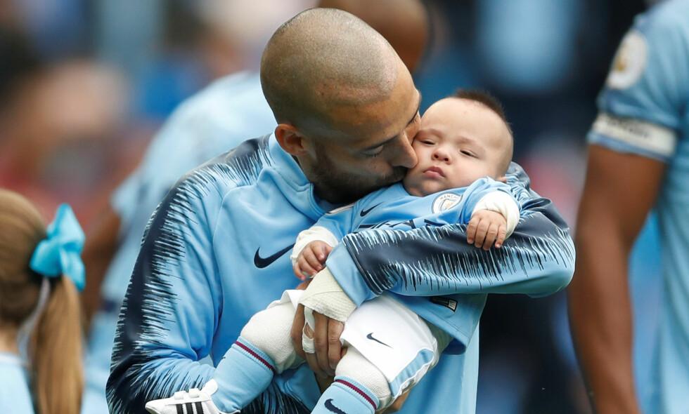 FAR OG SØNN: David Silva hadde med seg sønnen Mateo (0) på kamp for første gang. Han fikk se pappa score og Manchester City vinne mot Huddersfield. Foto: Reuters / Carl Recine