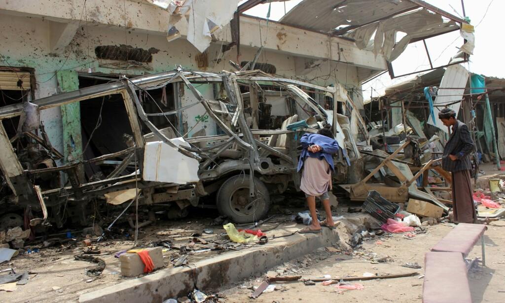 RESTENE: En ung gutt undersøker restene av skolebussen der flere titalls andre barn ble drept. Skolebussen ble angrepet fra lufta, av et saudiarabisk fly, bevæpnet med amerikanske bomber. Foto: AFP / NTB Scanpix