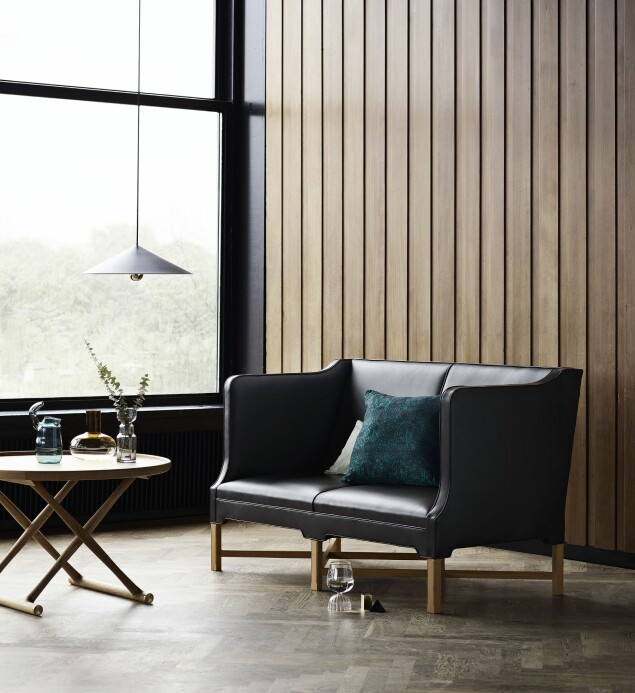 Trenden med å legge panel på hele veggen gir lun bakgrunn for møbler og en vakker kontrast til både skinn og blanke metaller. Den klassiske «2213»-sofaen fra Børge Mogensen forhandles av Fredericia.