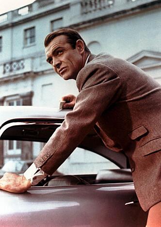 <strong>LEGENDE:</strong> Goldfinger var den første filmen med Aston Martin DB5. Bak rattet satt Sean Connery, som ikke hadde noen problemer med å kjøre fra en Ferrari på svingete veier. Foto: Mary Evans Picture / NTB Scanpix