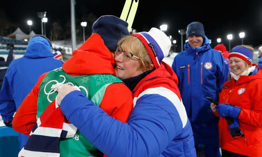 FORTJENER OGSÅ EN KLEM: Trine Skei Grande gratulerer Johannes Høsflot Klæbo med OL-gull. Seinere har kulturministeren i praksis vist hvorfor også hun fortjener enklem for innsatsen for Norge. FOTO: AFP/Odd Andersen.
