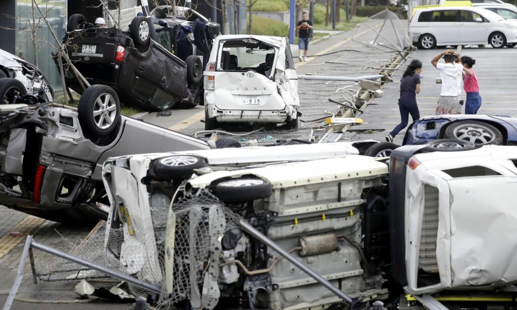 VOLDSOM VIND: Småbilene hadde ikke en sjanse mot vindkastene. Dette bildet er fra Osaka i dag. Foto: AP / NTB Scanpix