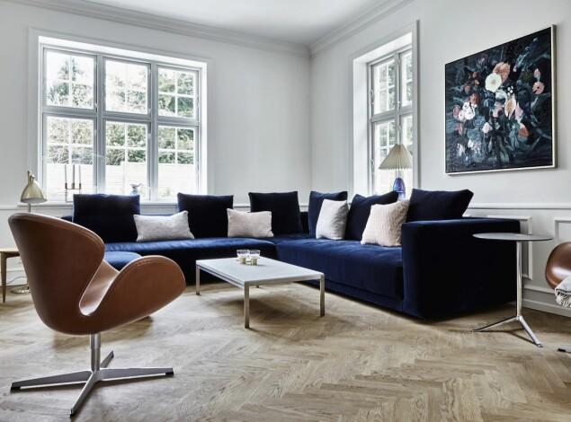 Sofaen i den dype, blå fargen er spesialdesignet av Eilersen, og Svanenstolene i konjakkfarget skinn er av Arne Jacobsen. FOTO: Lene Samsø