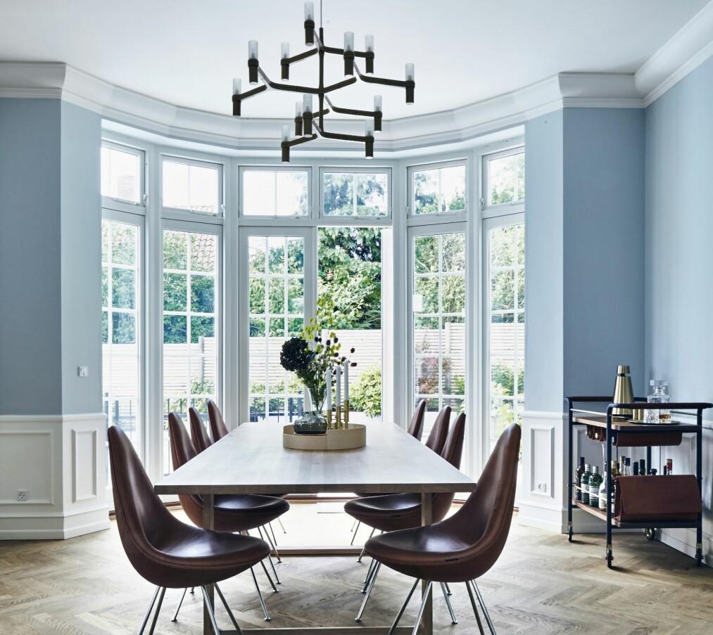 <strong>INTERIØR:</strong> La yndlingsfargen slå an tonen i et rom. Her er det lyseblå som gir kjølig kontrast til interiøret i tre, skinn og gyllen messing. Spisebordet er designet av Cecilie Manz, og stolene er av typen «Dråpen», designet av Arne Jacobsen. Lampen «Crown Minor» er fra Nemo og rullebordet «Valet Bar Cart» er fra Stellar Works. Veggmalingen er fra Farrow and Ball. FOTO: Lene Samsø