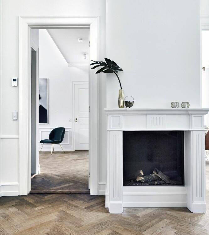 Skap stemning med en biogasspeis i klassisk forkledning. I en helt nybygget villa med minimale varmeutgifter gir det ikke alltid mening å installere en peis for å varme opp stuen, men åpne flammer gir hygge. Gjennom døren kan man se inn til hallen. FOTO: Lene Samsø