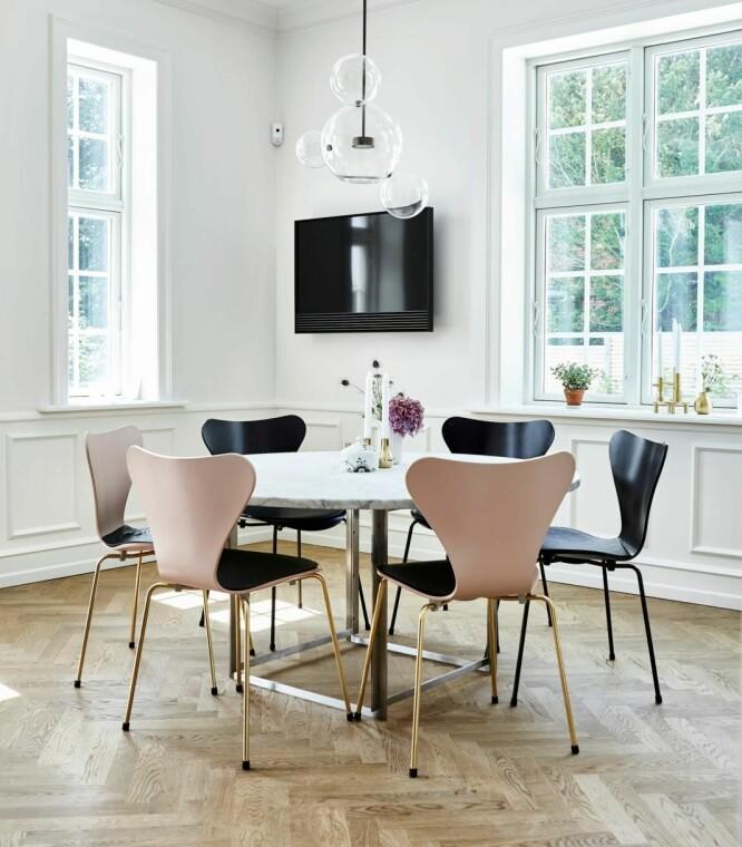 Utradisjonelle farger og moderne, lett design gjør klassiske rammer mindre konservative, som for eksempel å velge rosa stoler og et rundt, tynt marmorbord. Lampen over bordet er fra Møller & Rothe og 7-er-stolene er fra Fritz Hansen. FOTO: Lene Samsø