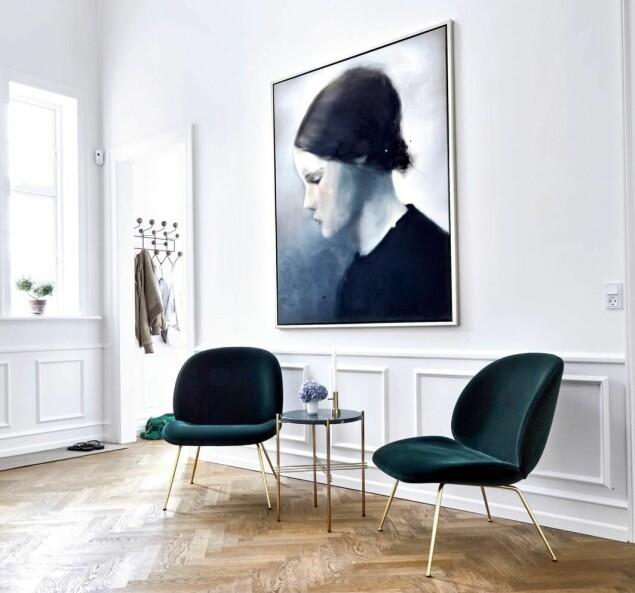Moderne kunst kan rocke opp det klassiske uttrykket. Det store maleriet «Når tanken er fri» av den danske kunstneren Siri Gindesgaard fikk hovedrollen i innredningen av den luftige hallen. Stolene i grønn velur fra Gubi er kjøpt for nettopp å kle kunstverket. FOTO: Lene Samsø