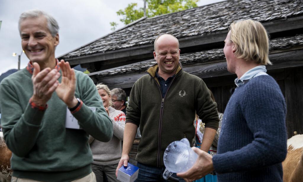 MUNTERT AVBREKK: AP-leder Jonas Gahr Støre og SP-leder Trygve Slagsvold Vedum ler og klapper etter at Petter Pilgaard drakk opp råmelken de nettopp hadde melket fra kua. De tre deltok i en melkekonkurranse under Dyrskun i Seljord. Foto: Tore Meek / NTB scanpix