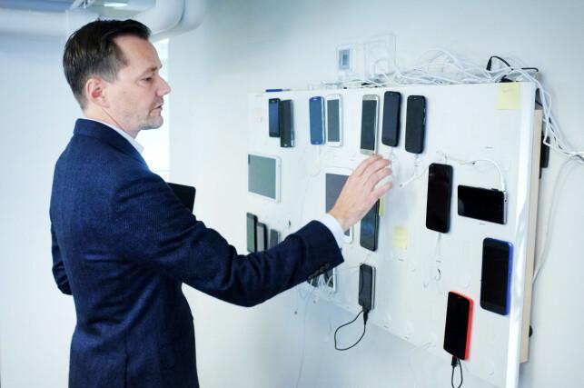 Jonas Rein Tovsen viser fram veggen som Shortcut bruker til å teste Android- og iPhone-appene sine på de fleste tenkelige skjermer. Foto: Ole Petter Baugerød Stokke
