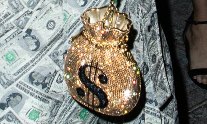 TILBEHØR: Antrekket ville selvfølgelig ikke vært komplett uten en pengesekk i gull. Foto: Splash News