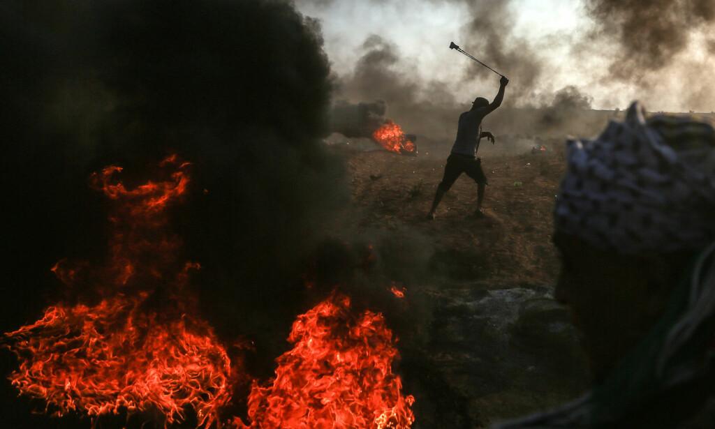 STORE DEMONSTRASJONER: En palestinsk demonstrant bruker sprettert for å skyte stein mot israelske tropper ved grensa mellom Israel og den hermetisk lukkede Gaza-stripa i går. Minst sju palestinere ble drept og mer enn 500 skadd i går, da rundt 20 000 palestinere demonstrerte ved Israel-grensa. Foto: Xinhua / Sipa / Scanpix