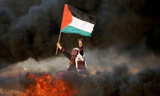 ALLE ER MED: Israel sier at demonstrantene nær grensa er væpnede Hamas-tilhengere, men palestinere i alle aldre er med. Her er en kvinne som viser fredstegn, samtidig som hun ber Israel heve blokaden inn til Gaza. Foto: Mohammed Salem / Reuters / Scanpix