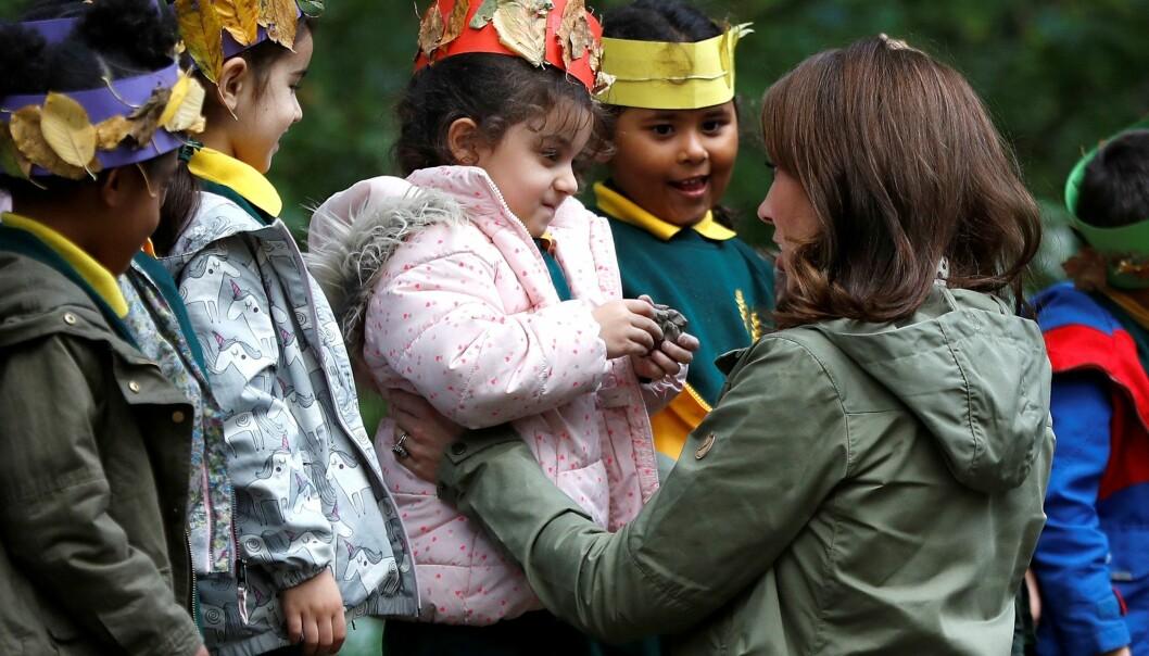 GLAD I BARN: Kate, som selv er trebarnsmor, viste at hun hadde barnetekke da hun hjalp barna med å lage, passende nok, «kroner» til barna av blader. Foto: NTB Scanpix