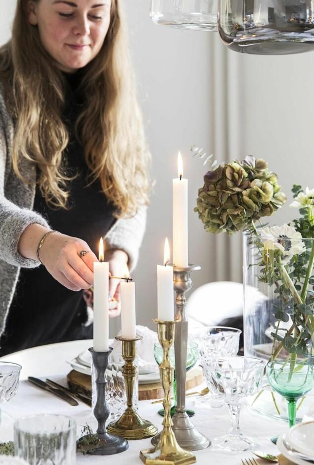 Lysestaker i forskjellige størrelser og en vase med franske anemoner, eukalyptus og hortensia pryder festbordet.