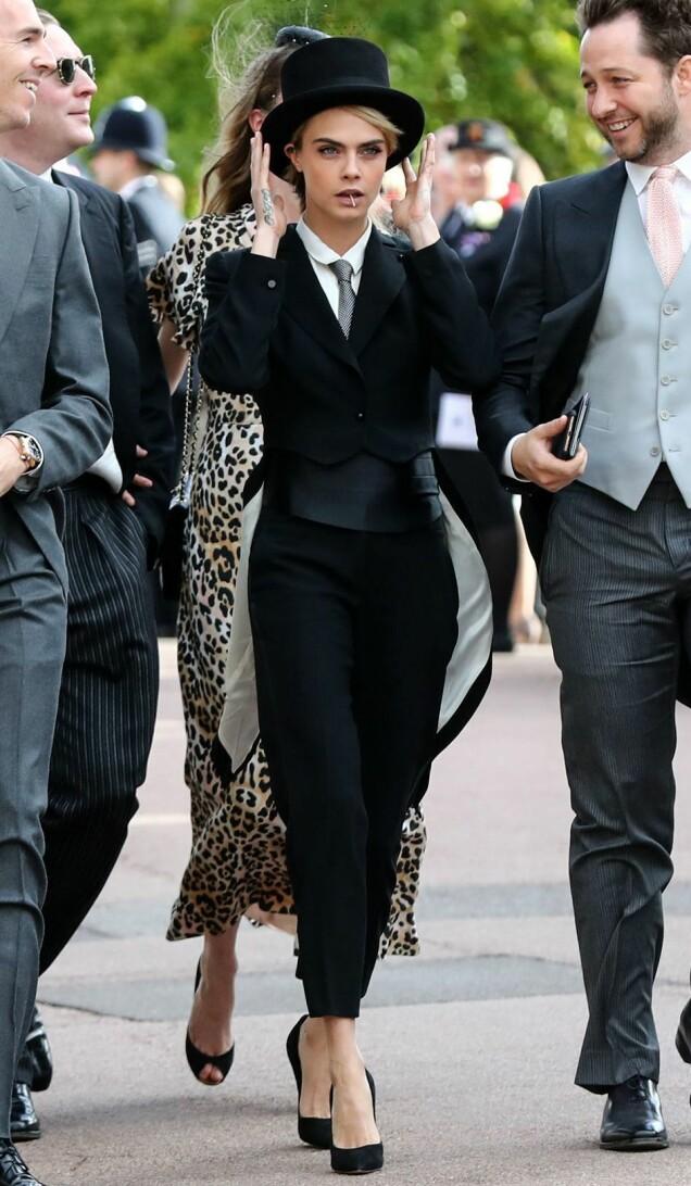<strong>ORIGINAL:</strong> Supermodell Cara Delevingne skilte seg ut i dress og flosshatt da hun ankom bryllupet. Foto: NTB scanpix