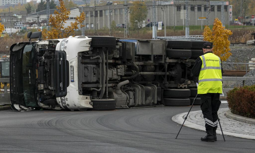 VELTET: Politiet og ulykkesgruppa til Statens vegvesen var på plass i Nedre Kalbakkvei i Oslo hvor et vogntog veltet i en rundkjøring fredag morgen. Foto: Tore Meek / NTB scanpix