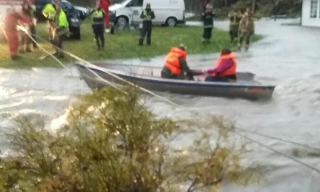 KORT, MEN DRAMATISK BÅTTUR: To medlemmer i familien Øygard kommer seg den korte veien over det flomstrie vannet i båten som er sikret med stram line av brann- og redningsmannskaper. Foto: Privat.