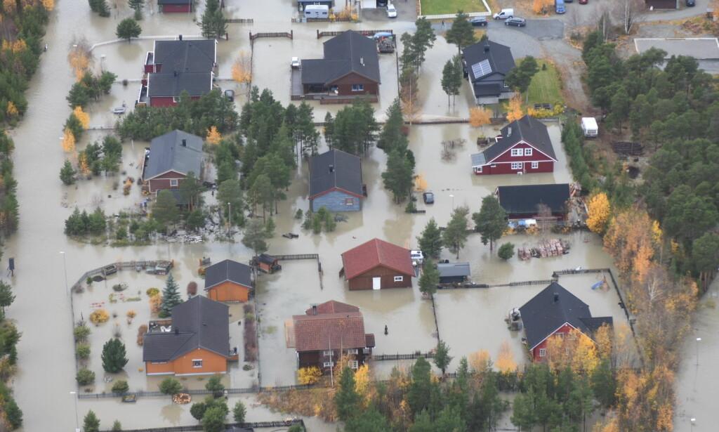 KATASTROFE: En rekke hus i Bismo i Skjåk står under vann. Ødeleggelsene er enorme. Foto: Politihelikopteret / NTB Scanpix