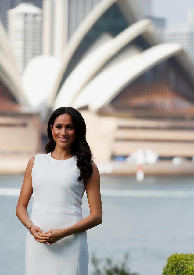 MEGHAN MARKLE: Den vakre hertuginnen matchet det berømte operahuset i Sydney (i bakgrunnen) i sin hvite kjole - som så vidt avslørte en liten antydning til babymage. Foto: NTB scanpix