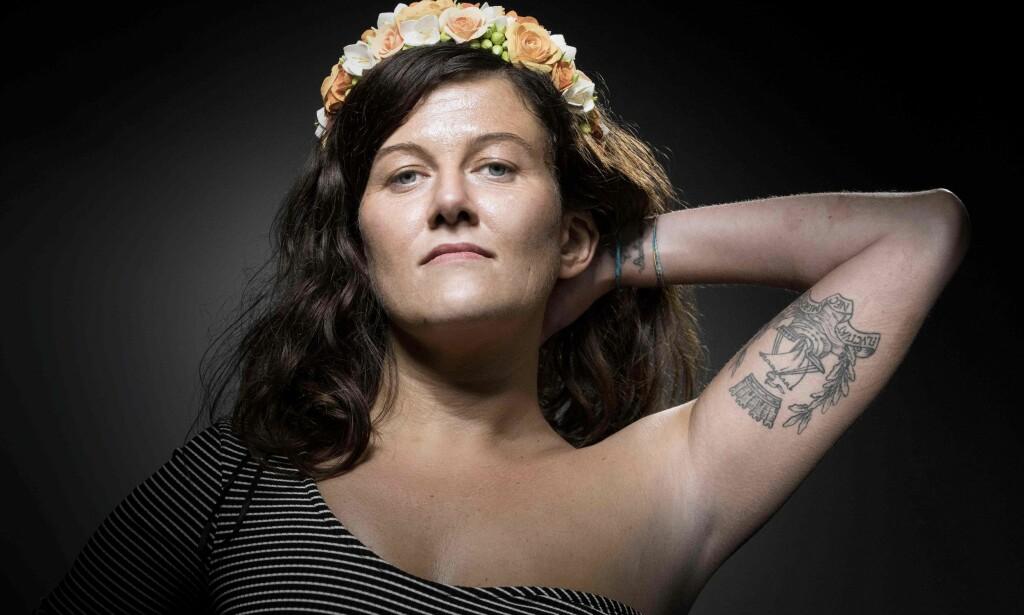 DØMT: På dette bildet viser Alexandra Damien fram tatoveringen som mange terrorofre tok i kjølvannet av Paris-angrepet i 2015. På tatoveringen står det «Fluctuat nec mergitur», som betyr «det gynger, men synker ikke». Foto: JOEL SAGET / AFP / NTB scanpix