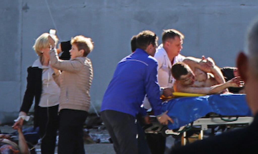 DØDELIG ANGREP: Redningsfolk hjelper skadde personer etter et dødelig angrep på en skole i havnebyen Kerch på Krim. Foto: Ekaterina Kejzo/Courtesy of Kerch./Handout via REUTERS/NTB Scanpix