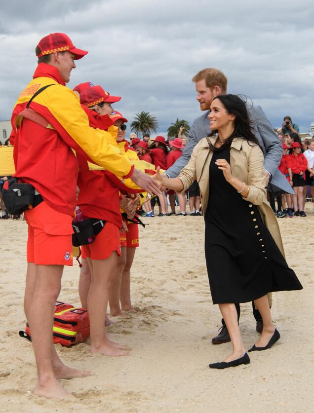 PRAKTISK FOTTØY: Også da hertugparet hilste på en strandpatrulje på stranden i Melbourne torsdag, var Meghan iført de falte skoene sine. Foto: NTB scanpix