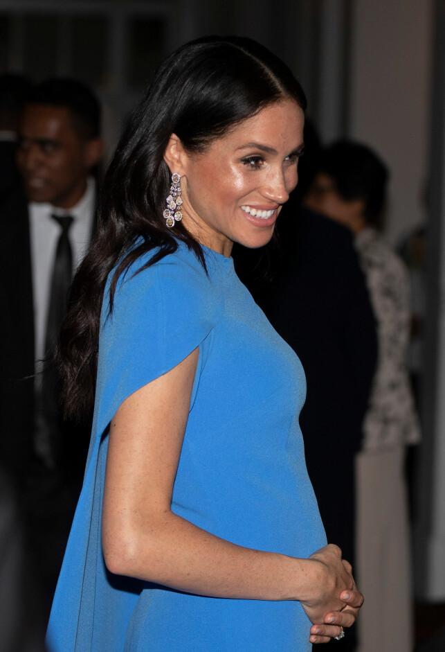 STRUTTET: Hertuginne Meghan viste stolt fram den voksende magen under gårsdagens middag i Fiji. Foto: NTB scanpix