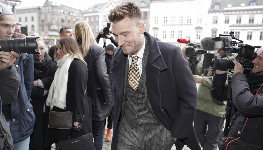BLID: Selv om danske Nicklas Bendtner potensielt sett kan risikere flere års fengsel, smilte han til pressen da han ankom retten i København i dag tidlig. Foto: NTB scanpix