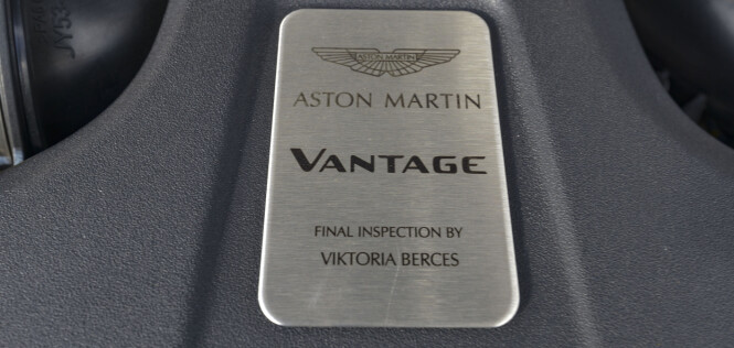<strong>V8 Biturbo:</strong> Vantage bruker AMG-s fantastiske 4-liters V8 md doble turboer. Den blir bygget av en mann hos AMG og signeres, men Aston Martin ønsket ikke noen spor av AMG og har laget en egen plakett. Victoria Berces har tydligvis inspisert motoren etter ankomst hos Aston Martin. Foto: Jamieson Pothecary