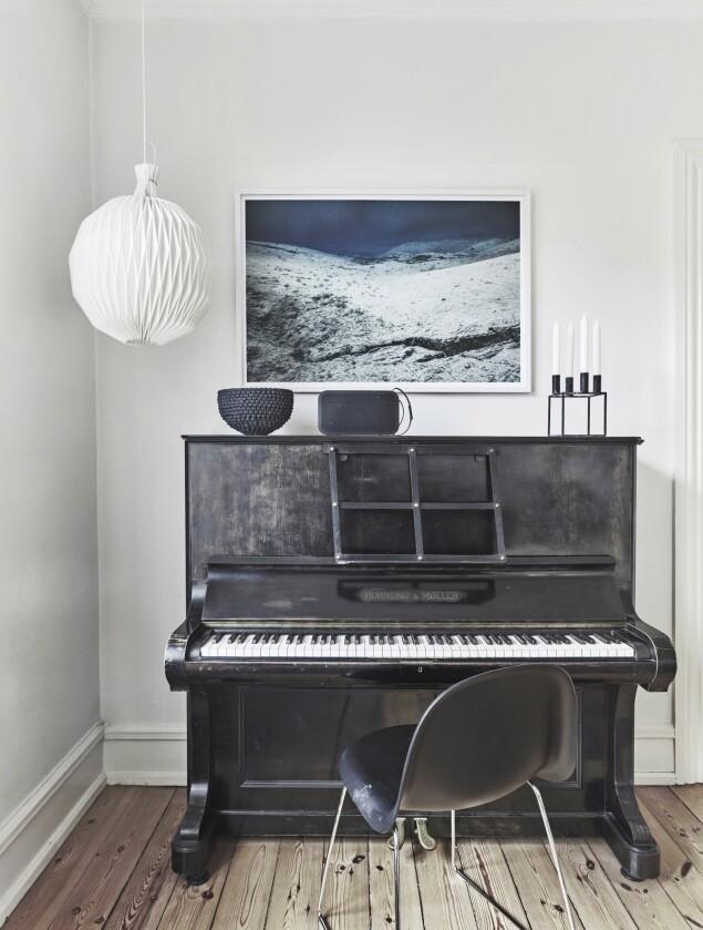 Stolen er fra Gubi, og lampen er fra Le Klint. På pianoet står keramikk av Stine Jespersen, Bang & Olufsens Beoplay og en kubusstage fra By Lassen. Fotokunst av Stig Stasig. FOTO: Birgitta Wolfgang