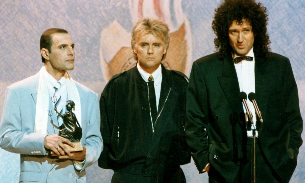 ÅRET FØR DØDSFALLET: Her har Freddie Mercury og «Queen»-kollegene Roger Taylor og Brian May akkurat vunnet pris under BRIT Awards i 1990. Året etter døde Mercury av sykdom i sitt eget hjem. Foto: NTB Scanpix