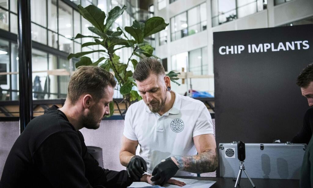 «BIOHACKER»: Jowan Österlund (i midten), er en tattovør og piercing-spesialist som nå har blitt en proffesjonell «biohacker». Her er han avbildet mens han implanterer en chip under en konferanse på Epicenter i Stockholm i januar i år. Foto: Jonathan Nackstrand / AFP / NTB Scanpix