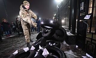 DEMONSTRASJONER: Etter det russiske angrepet på krigsskipene, oppsto det opptøyer da rundt 150 demonstranter samlet seg utenfor den russiske ambassaden i Kiev. Her kaster en demonstrant et bildekk på et bål. Foto: AFP / Reuters