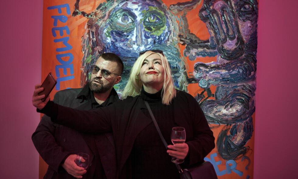 SELFIE PÅ ÅPNINGEN: Det er alltid folksomt når Bjarne Melgaard åpner ny utstilling. Kunstnerkollega Unni Askeland dokumenterer vernissasjen med en selfie og poserer foran et av de mange, store bildene. Foto: Anders Grønneberg
