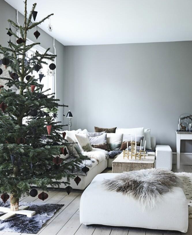 Synes du det blir for stilrent å pynte treet med støvete, mørke farger som her, kan du jo begynne med det, og heller supplere med barnas hjemmelagde pynt julaften.  Sofa og puff er fra Eilersen, mens sofabordet er fra Rosmosegaard og de gylne Nagel-stakene fra Stoff. FOTO: Mette Wotkjær