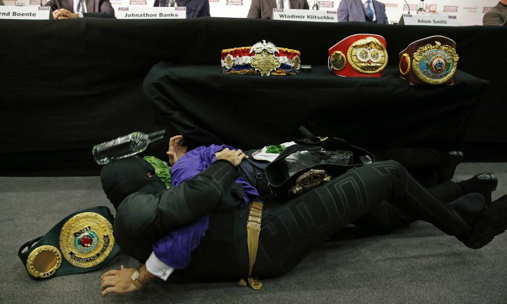 BATMAN OG THE JOKER: Tyson Fury rullet rundt forkledt som Batman i en kamp mot erkefienden The Joker så beltene til Klitsjko datt ned fra utstillingsbordet, og ei flaske deiset i hodet på Fury. Foto: Reuters / NTB Scanpix