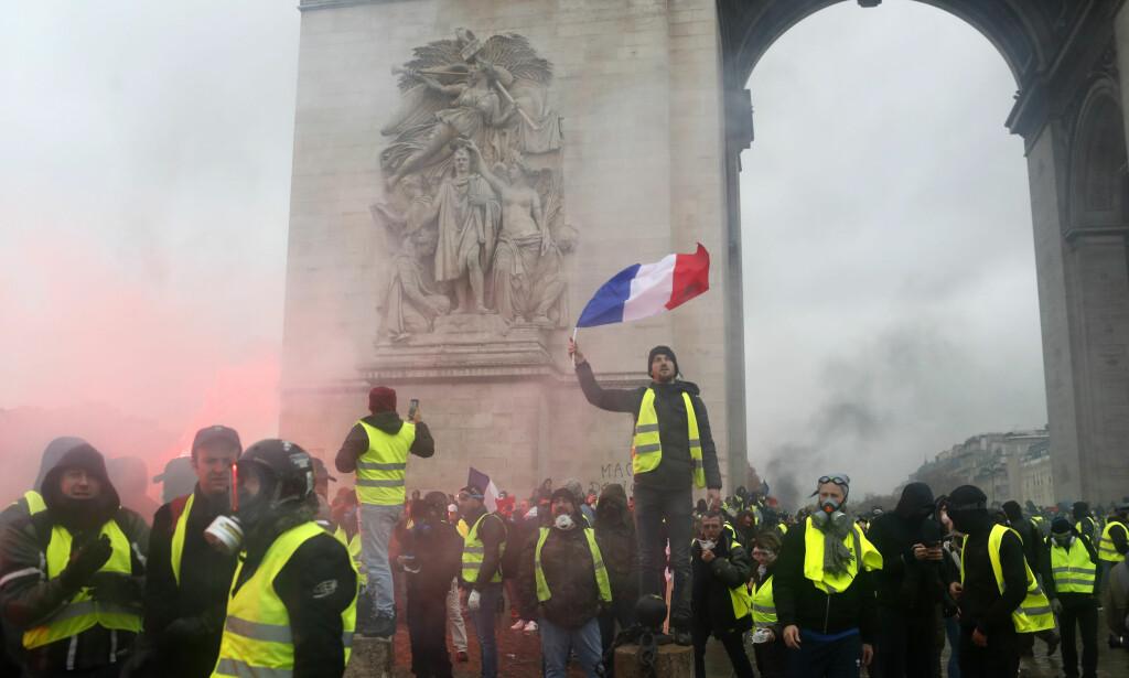 DEMONSTRERER: Demonstranter fra protestbevegelsen De gule vestene protesterer ved Triumfbuen i Paris mot økte drivstoffavgifter. Foto: AP / NTB scanpix