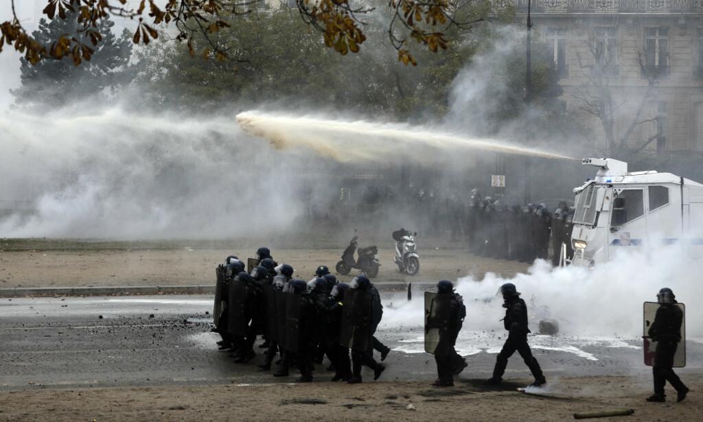 TÅREGASS: Fransk opprørspoliti brukte vannkanoner og tåregass for å spre demonstrantene i Paris. Minst 140 demonstranter ble pågrepet. Foto: AP / NTB scanpix