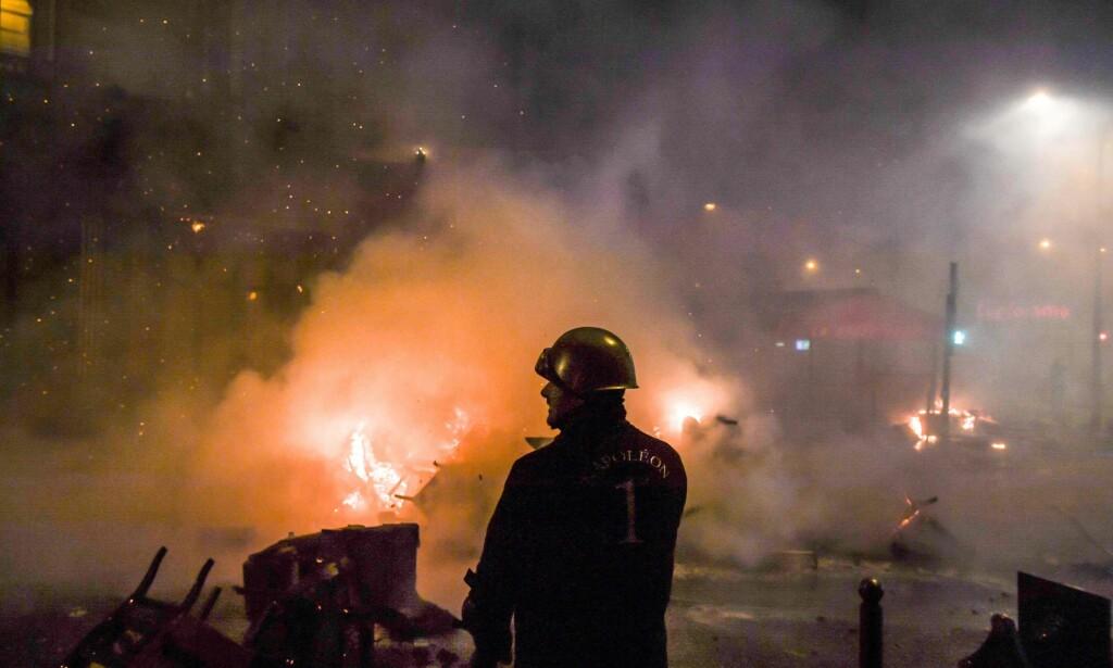 «KRIGSSONE»: En brannmann er avbildet ved en av de mange brannene i Paris lørdag. Den danske presten Selma Ravn beskriver scenene i den franske hovedstaden som en krigssone. Foto: AFP / NTB Scanpix